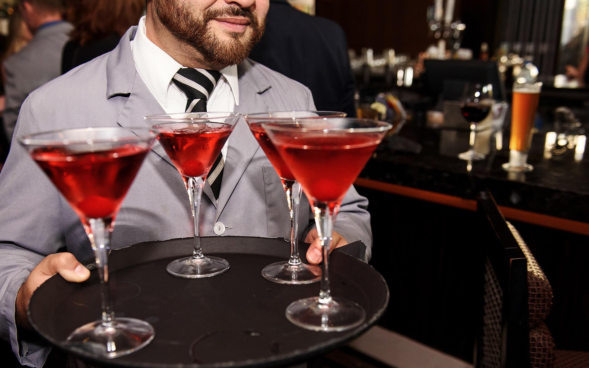 Stilvoller kann man Cocktails kaum servieren: Kellner mit Martini-Gläsern